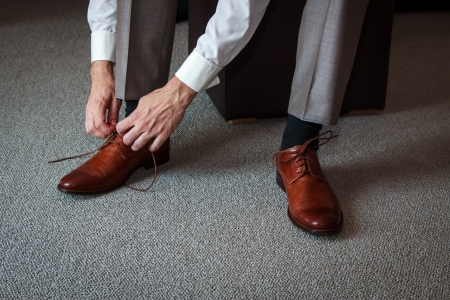 shoelaces: A young man tying elegant shoes indoors