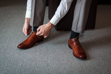 tying: A young man tying elegant shoes indoors