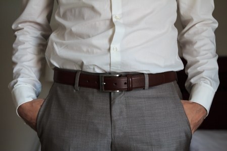 A man with elegant trousers and shirt and a brown belt