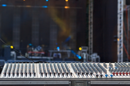 A mixing console in front of a stage