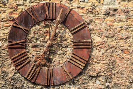 A rusty old clock on a stone wall in Zagreb, Croatia photo