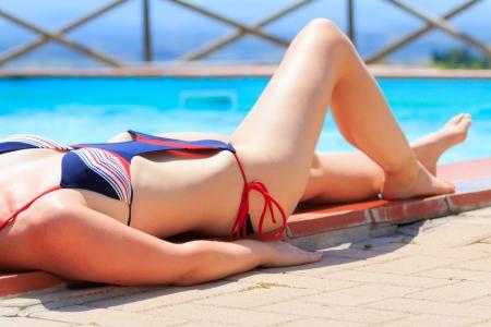 monokini: Female beautiful body in a bikini sunbathing next to a pool Stock Photo
