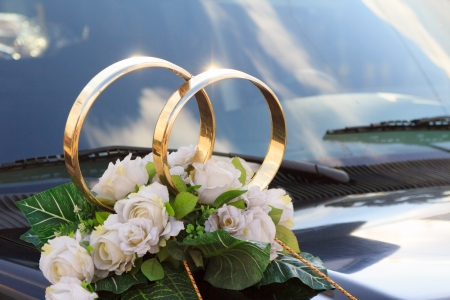 A flower arrangement with big golden rings for a wedding on a black car Imagens