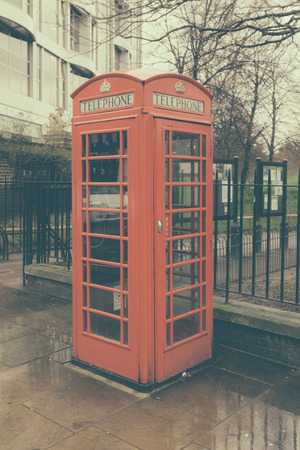 A traditional red telephone booth on a rainy day in London, UK in retro style photo