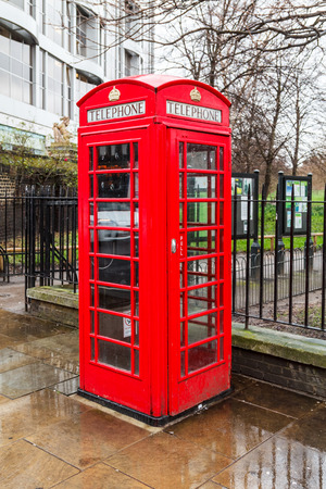 A traditional red telephone booth on a rainy day in London, UK photo
