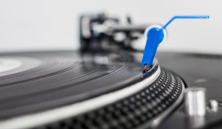 Closeup of a DJ needle on black vinyl record on a classic turntable photo