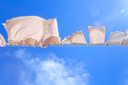 clothes pegs: Pieces of laundry on a washing line on blue sky blown by the wind Stock Photo