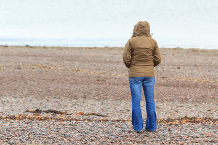 A lonely woman in a rain jacket, cagoule staring at the sea on a windy gravel beach in Scotland