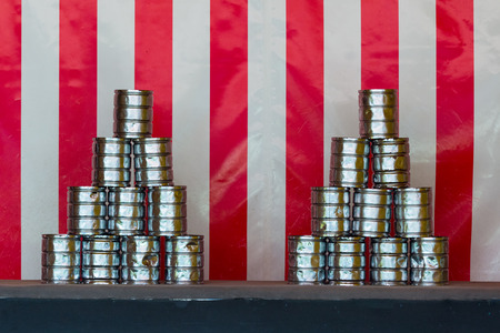 Two pyramids of tin cans for throwing balls at them on red white striped background Imagens
