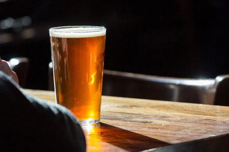 An english ale in front of an individual on a wooden table in a pub in London, UK Imagens