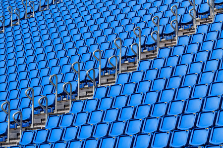 Stadium seating with blue folded up chairs Stock Photo