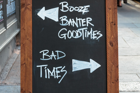 bad times: Chalk board in front of a pub with good times versus bad times