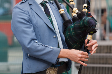 piper: A closeup of the upper part of the body of a scottish piper playing the bagpipe