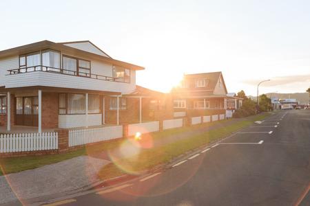zona: Puesta de sol sobre casas de familia en una zona suburbana en Whitianga, Nueva Zelanda