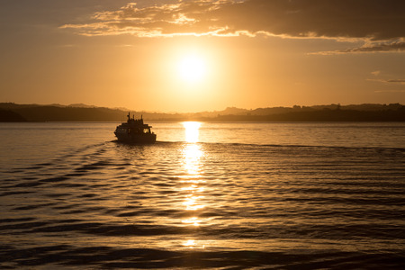 A silhouette of a ferry departing from the harbor at sunset in Russell, New Zealand photo