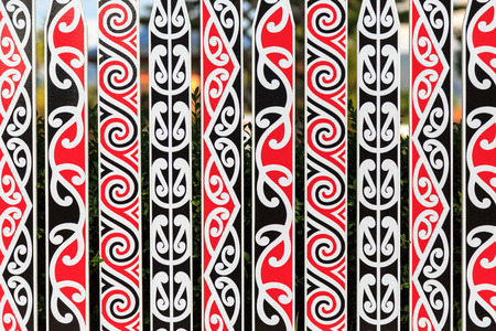 An ornate fence with a typical Maori pattern in red, white and black in Rotorua, New Zealand