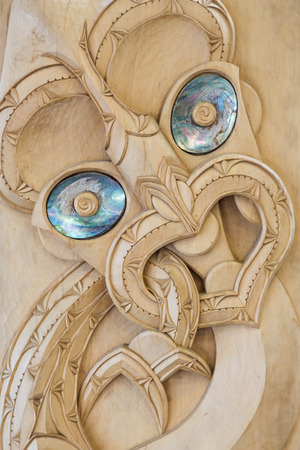 Wooden Maori carving symbolizing an ancestor with the typical paua shell in the eyes without paint in Te Puia, Rotorua, New Zealand Stock Photo