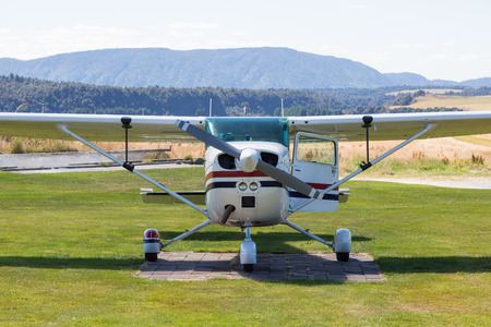 Front of a small passenger plane with propeller and open door on a grass airport in the country of New Zealand