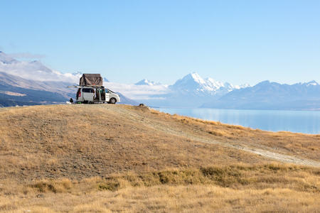 A camping van with a tent in front of lake Pukaki and Mount Cook
