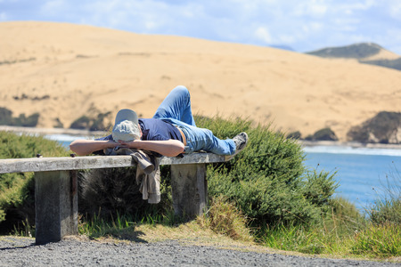 A man with a hat lying and relaxing on a bench opposite sand dunes in Arai-te-uru recreation reserve in Hokianga bay, New Zealand photo