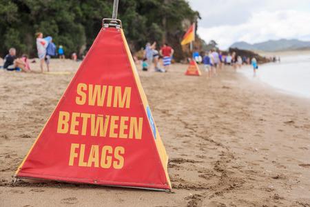 señales de seguridad: Un cono con una recomendación de seguridad: nadar entre las banderas en la playa de Agua Caliente cerca de Hahei, Nueva Zelanda