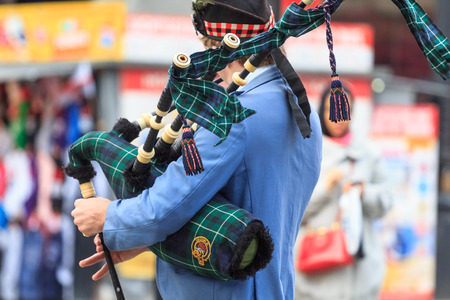scot: A closeup of the upper part of the body of a scottish piper playing the bagpipe