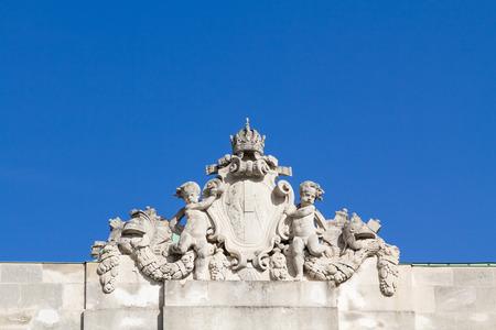 angeles bebe: Los ángeles del bebé ornamentales sosteniendo un escudo real en la biblioteca nacional de los Austrias Foto de archivo