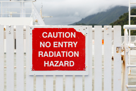 radiation hazard sign: A red weathered sign on a white gate: caution no entry radiation hazard