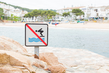 A sign indicating that jumping into the water is not allowed - Tamariu, Spain Stock Photo