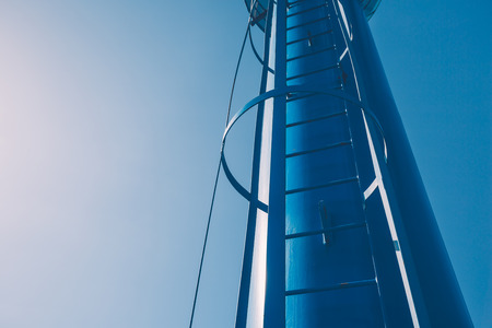 Closeup of a secured ladder on a blue metal tower
