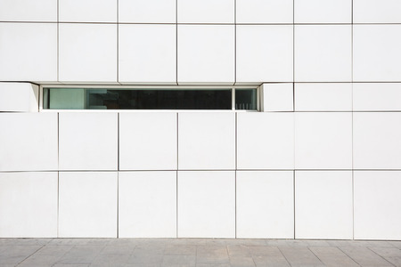 Clear modern white facade with a narrow window in Barcelona, Spain