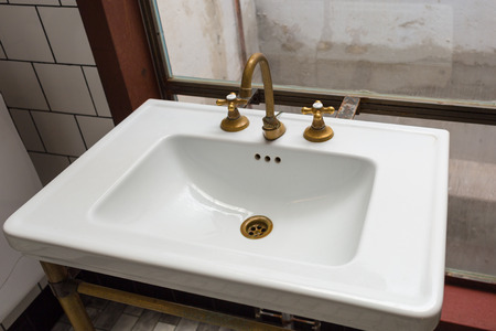 A vintage sink with golden separate tap and faucet Imagens