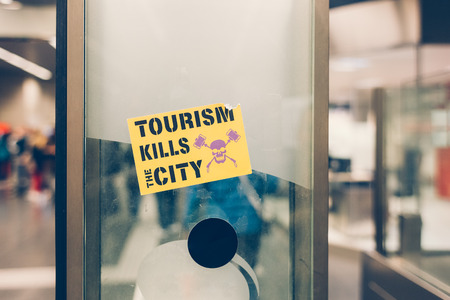 Tourism kills the cirty sticker in a public underground area in Barcelona, Spain