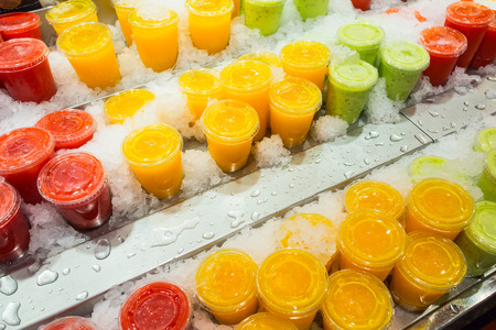 Fresh and healthy kiwi, berry and pineapple fruit juice in closed plastic cups on cold ice at a market