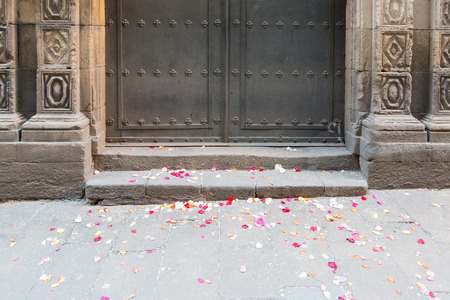 Colorful rose petal on the floor in front of an old closed church after the wedding in Barcelona, Spain Imagens