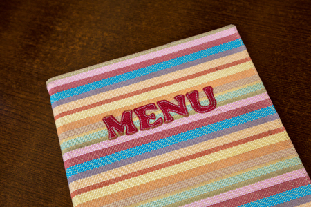 Colorful menu with knit cover on a table of a restaurant in Kotor, Montenegro