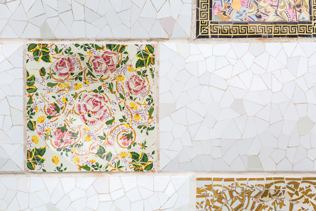 Colorful broken tiles mosaic with floral pattern at Parc Guell, Barcelona, Spain