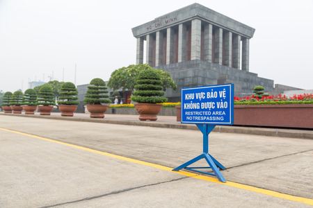 Blue sign for restricted area (no trespassing) in vietnamese and english behind a yellow line in front of the Ho Chi Minh mausoleum in Hanoi, Vietnam