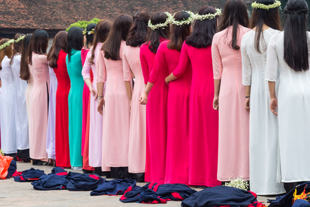 Female students from behind at a graduation ceremony behind an asian dragon sculpture at the temple of literature in Hanoi, Vietnam