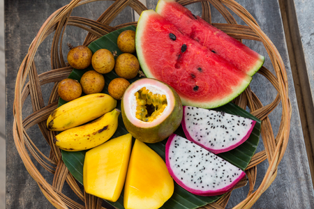 A fruit basket for breakfast with water melon, dragon fruit, mango, passion fruit, banana and longan from above Imagens