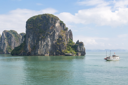 A small boat in Halong Bay next to a typical rock