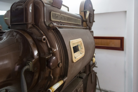 An old analog movie projector from behind Imagens