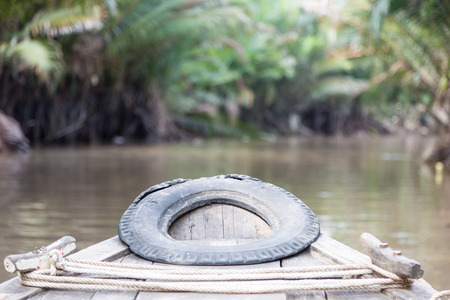 Front of a small wooden boat on a river in the jungle of the Mekong Delta, Vietnam
