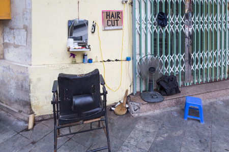 Open shop of a hairdresser at the corner of a building in Hanoi, Vietnam Imagens
