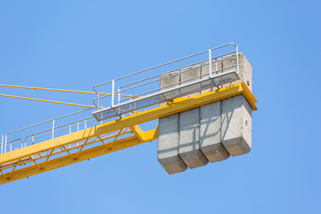 Concrete massive counterweight of a crane on blue clear sky Imagens