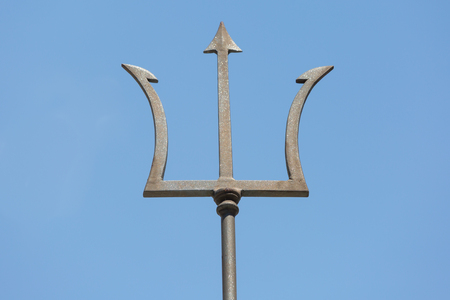 Top of an old metal trident of a neptune statue on blue sky in Triest, Italy