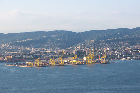 The modern industrial harbor with yellow cranes in Triest, Italy Imagens