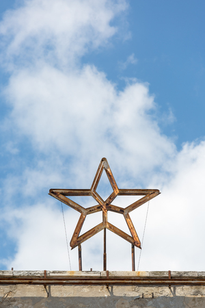 Ruined rusty metal star with broken neon lights on top of a building in Triest, Italy