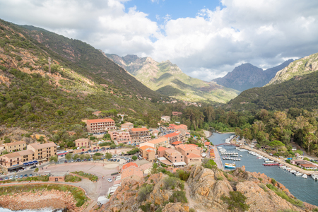Town and marina in front of the mountains in the bay of Porto in Ota, Corsica, France Imagens - 84774087