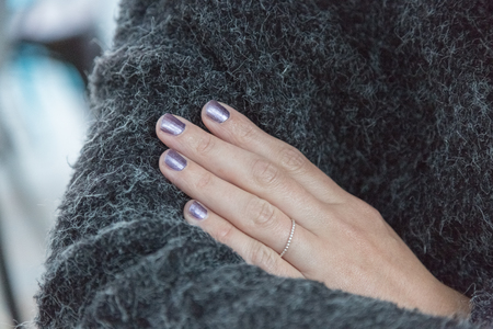 Purple painted shiny and glittering fingernails of a woman with folded arms and a warm vest